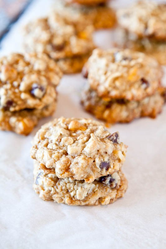 Multiple stacked Coconut Oatmeal Toffee Cookies on white parchment