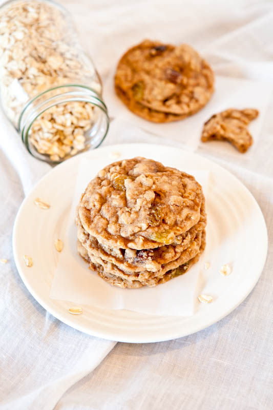 Stacked Oatmeal Raisin Cookies on white plate with jar of oats in background