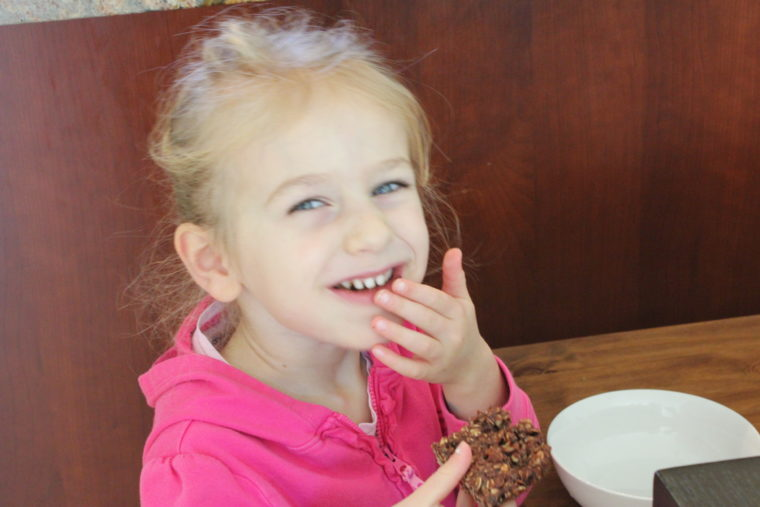 Young girl eating bar and smiling