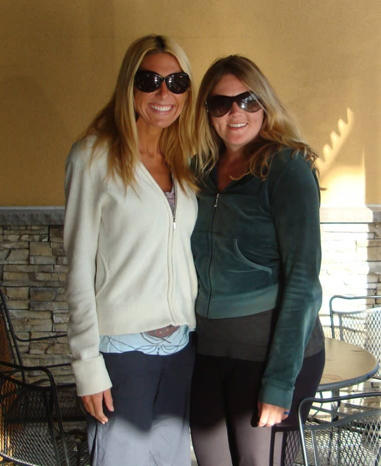 Two women with sunglasses standing smiling