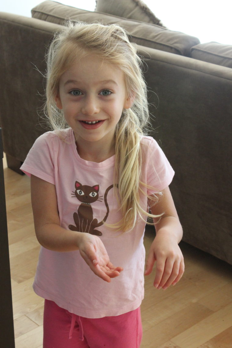 Young girl standing in pink cat shirt smiling