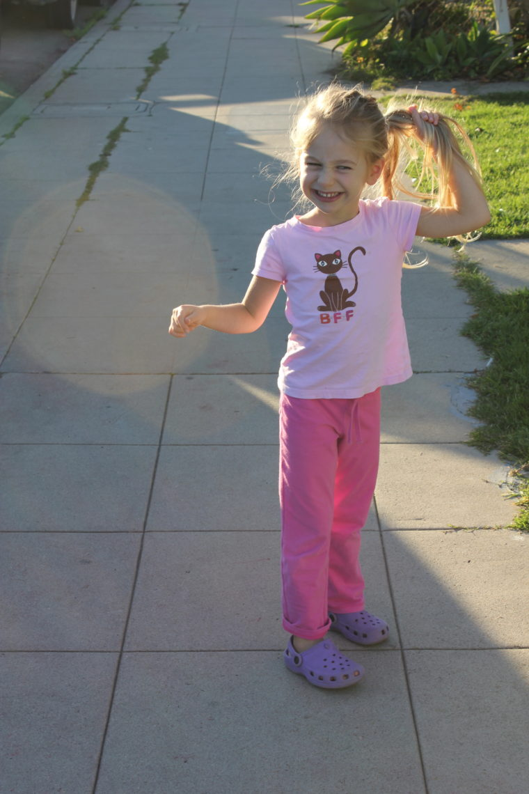 Young girl walking down the side walk playing with hair and smiling