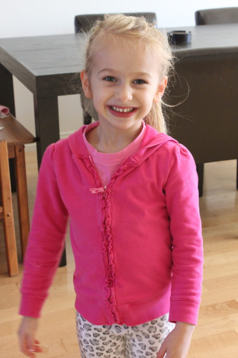 Young girl in pink zip up sweater smiling