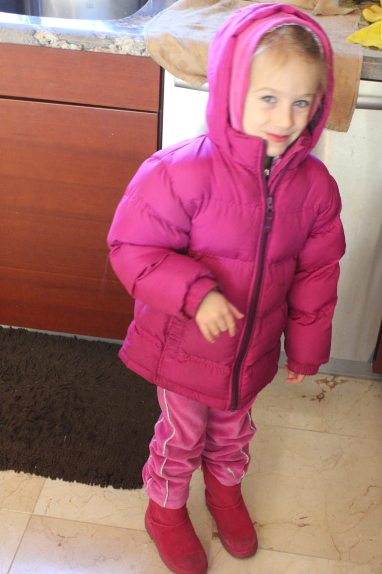 Young girl bundled up in pink jacket and boots