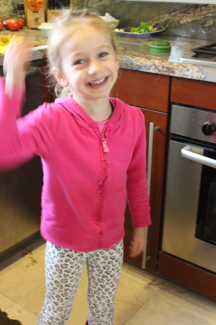 Young girl in kitchen smiling with hand up