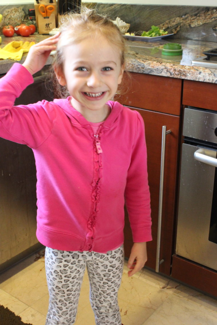 Young girl in kitchen smiling with hand on head