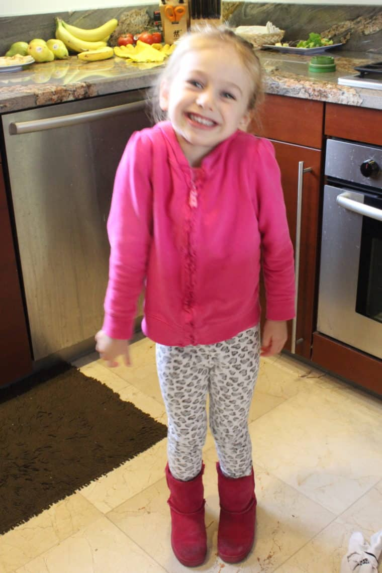 Young girl in kitchen wearing pink and smiling