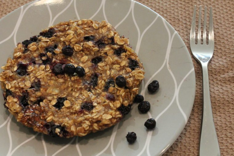 Microwave Blueberry Banana Oat Cake on plate topped with more blueberries