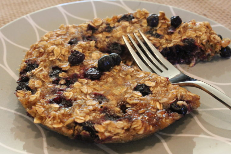 Microwave Blueberry Banana Oat Cakes with slice taken out on plate with fork