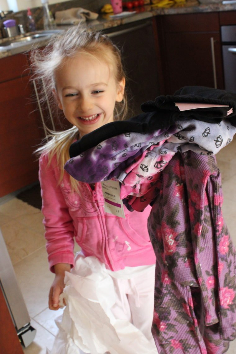 Young girl holding a bunch of new clothes