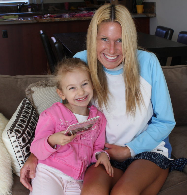 Woman and young girl on couch smiling while girl holds card