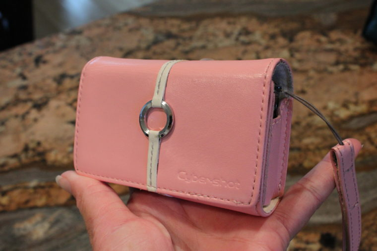 Side view of pink camera case with carrying strap