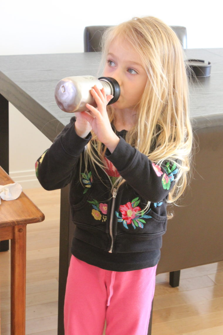 Young girl drinking from reusable drink bottle