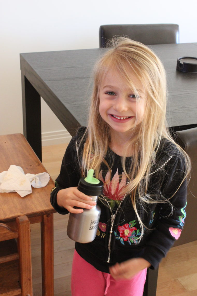 Young girl with hair down smiling and holding a reusable drink bottle