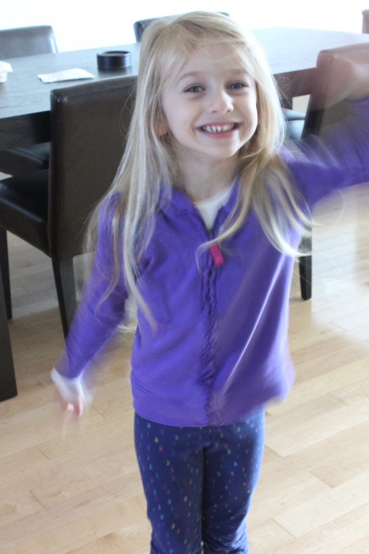 Young girl in dining room dancing with hair down