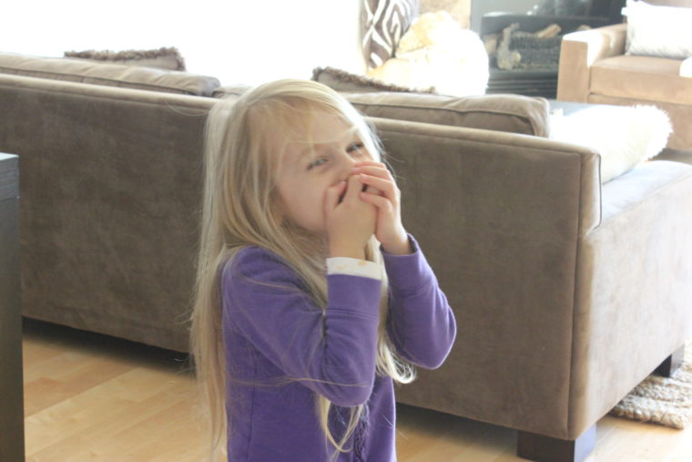 Young girl covering her mouth laughing