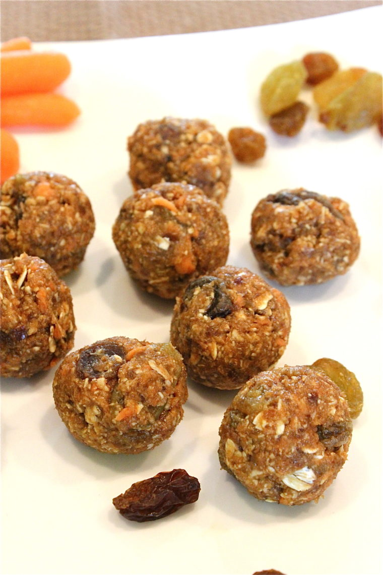No-Bake Oatmeal Raisin Carrot Cake Bites on white plate with raisins and carrots