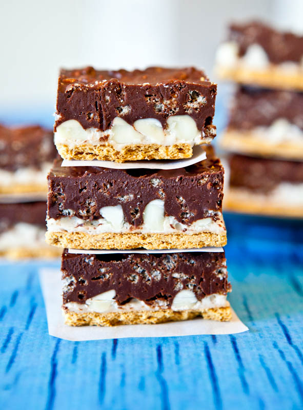 Side view of stacked Peanut Butter Cocoa Krispies Smores Bars separated by parchment paper