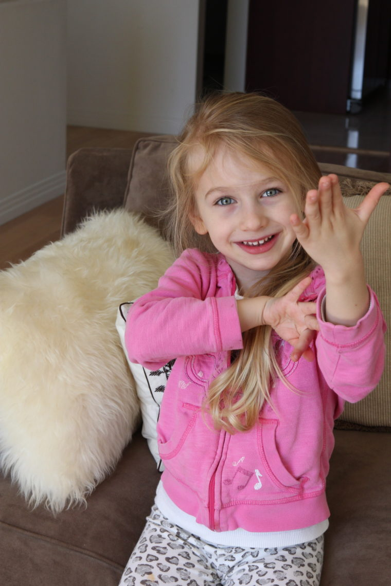 Young girl sitting on couch with arm up smiling