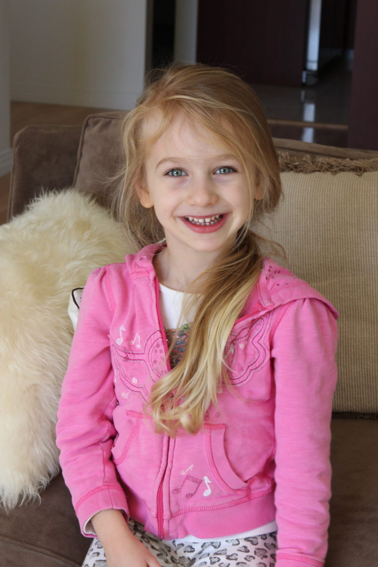 Young girl wearing pin and a pony tail sitting on couch smiling