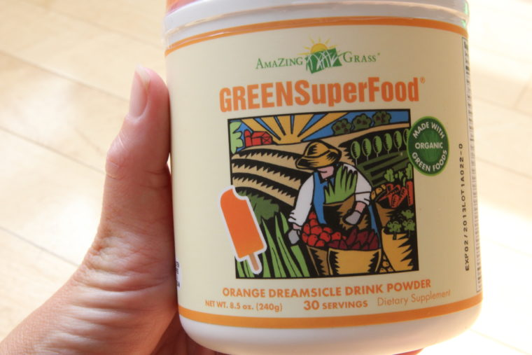 Hand holding container of Green Super Food in Orange Dreamsicle Drink Powder