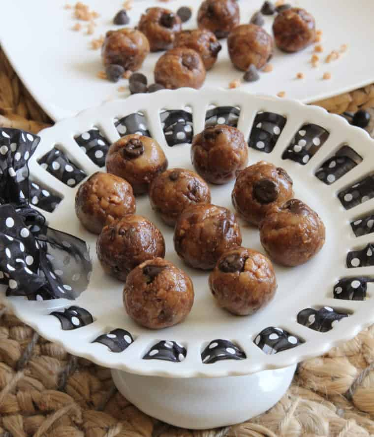 No Bake Toffee & Chocolate Chip Cookie Dough Bites on cake stand with more on plate in background