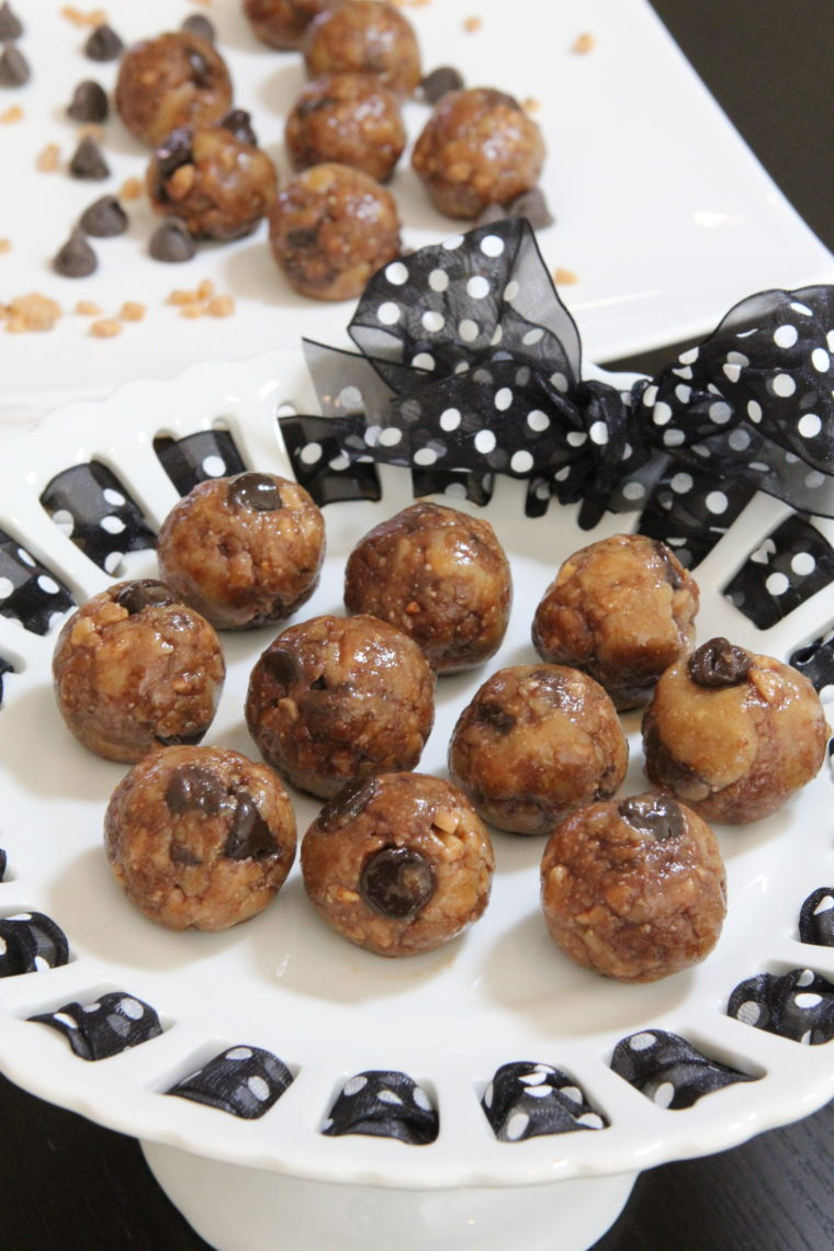 Close up of No Bake Toffee & Chocolate Chip Cookie Dough Bites on stand with bites on plate in background