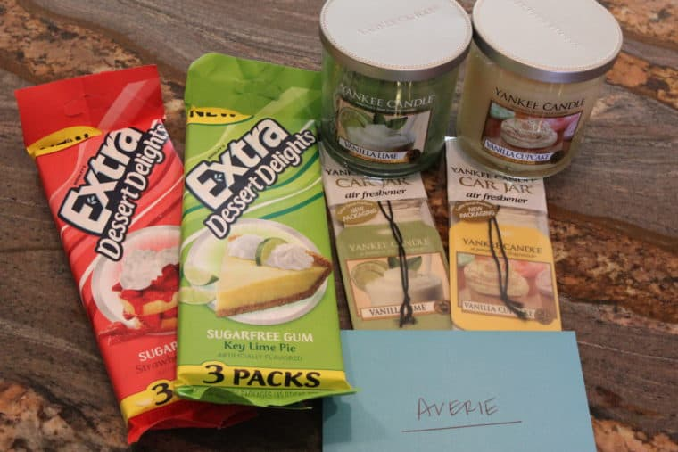 Candles, air fresheners and gum with card on countertop