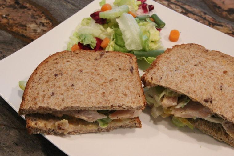 Split sandwich with side salad on plate