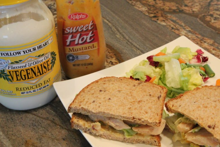 Sandwich on plate with jar of Vegenaise and Bottle of Sweet Hot Mustard