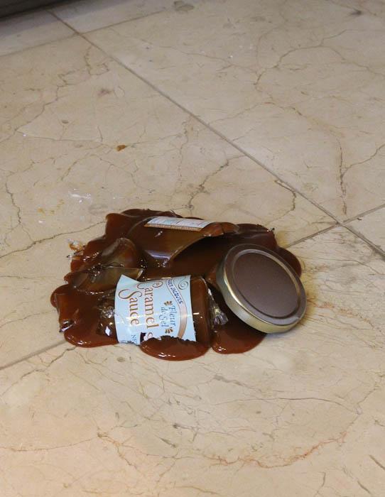 Broken jar of Carmel Sauce on floor