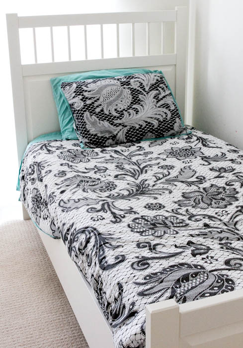 Girls bed with black, white and teal bedding