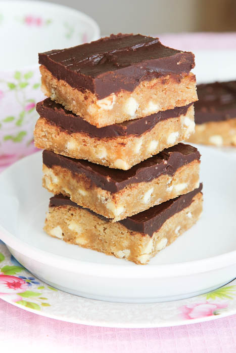 Bars with chocolate frosting stacked on white plate