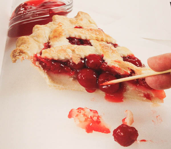 Page in book making a slice of cherry pie look appetizing