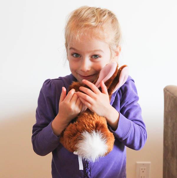 Skylar hugging brown bunny plush