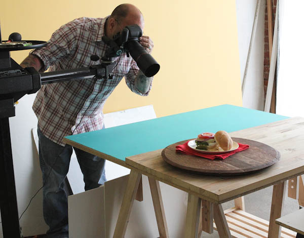 Man taking picture of food with large camera: food sitting on circular panel of wood