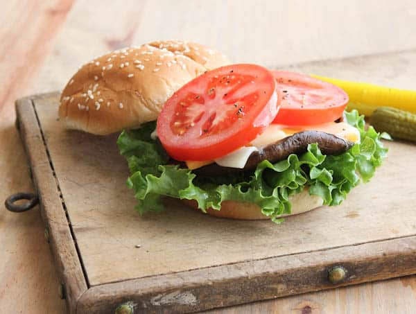 open hamburger with tomatoes, mushroom, cheese, and lettuce