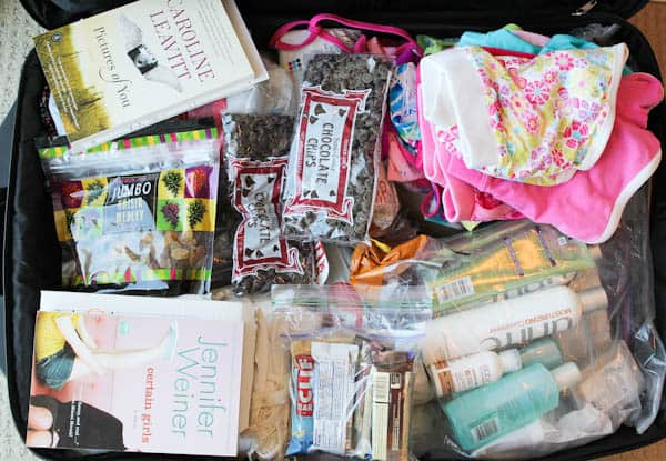 Packed suitcase of baking supplies and books