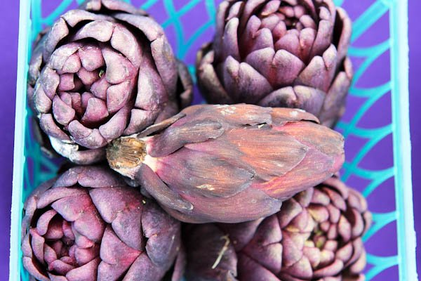 Overhead of stacked blue artichokes