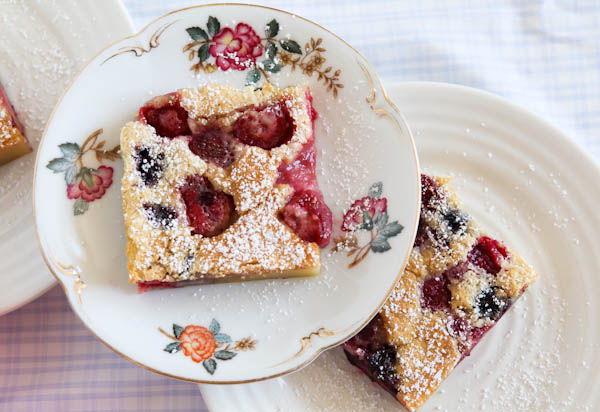 Slices of Mixed Berry Clafoutis on white plates stacked