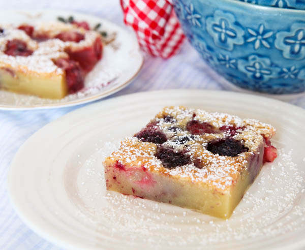Close up of Mixed Berry Clafoutis with a slice on plate in background