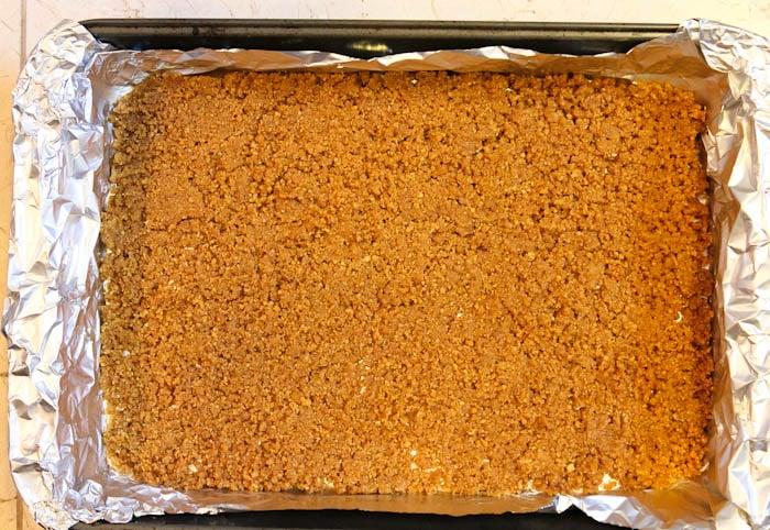 graham cracker crumbs in foil lined pan