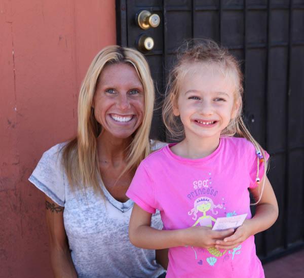 Woman kneeling next to young girl in front of door smiling