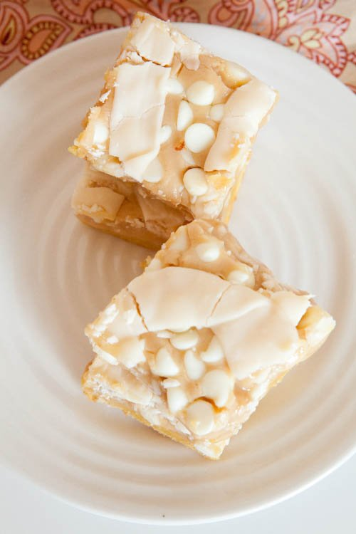 Four White Chocolate Vanilla Marshmallow Cake Bars on white plate stacked