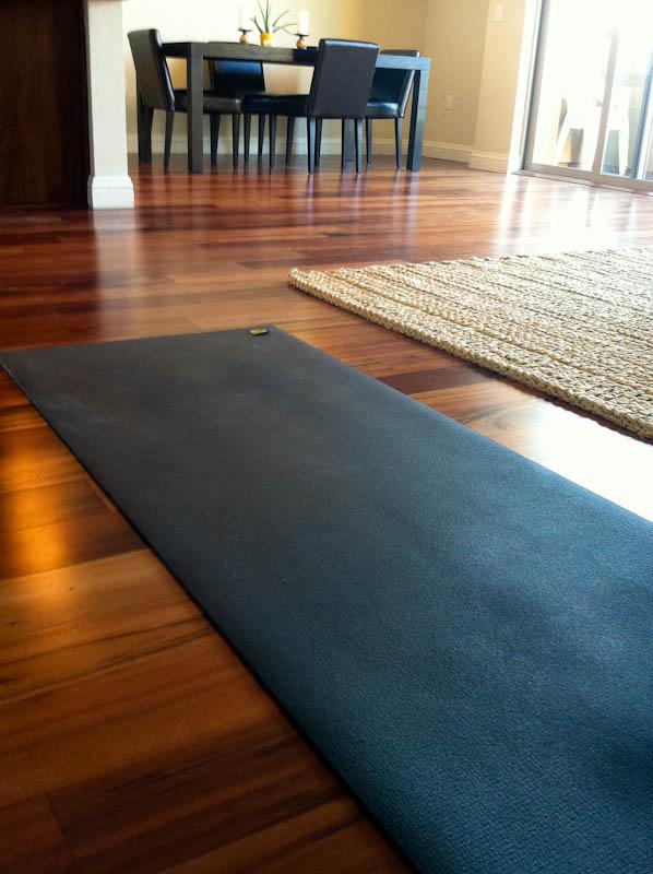 Black yoga mat on hardwood floor
