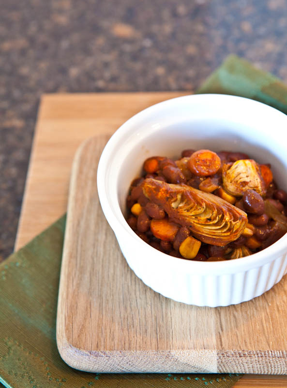 Ramekin filled with Spicy Baked Black Beans with Vegetables on cutting board
