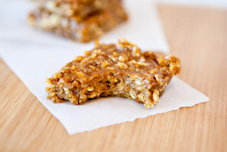 One Pumpkin Peanut Butter Oatmeal Bars on parchment paper with bite taken out