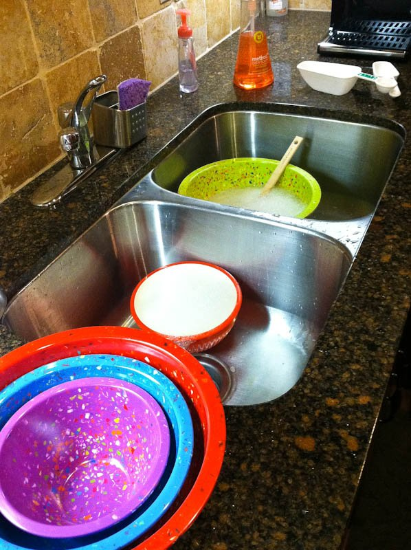 Sink full of bowls, red, blue and purple bowls stacked next to sink