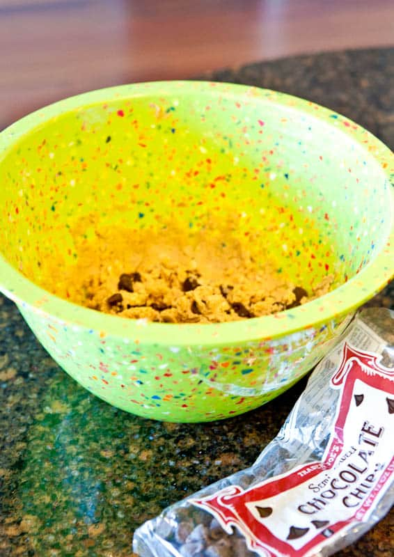 Raw cookie dough in yellow mixing bowl