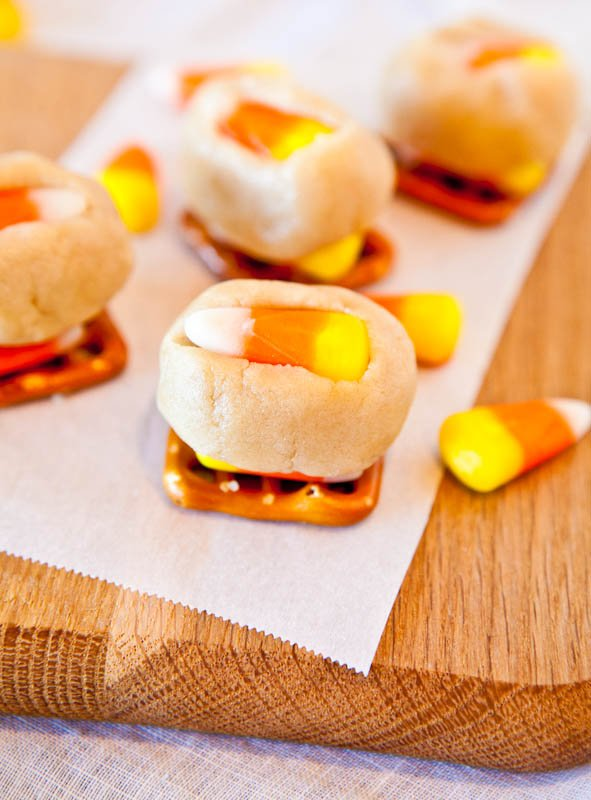 Candy Corn Cookie Dough Pretzel Bites on wood plank with candy corn around